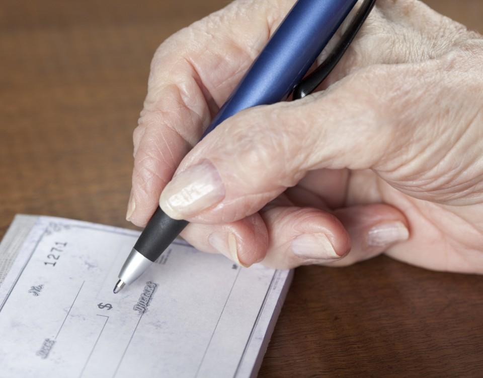 senior woman's hand writing bank check